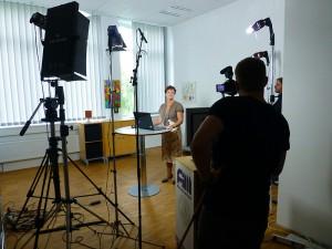 Der erste Video mit Monika wird gedreht. Die Scheinwerfer sind auf sie gerichtet und die Kameras laufen.