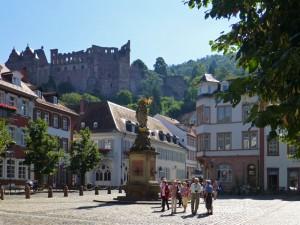 Der Kornmarkt in der Altstadt von Heidelberg mit Madonnenstatue und Schloss-Silhouette